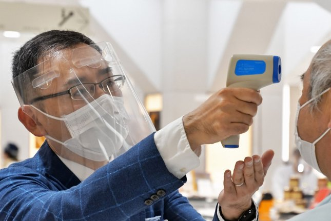 An employee wearing a face shield and face masks uses an infrared thermometer to check the temperature of customers at the entrance of the Matsuya Ginza department store, which partially reopened in Tokyo on Monday. Photo by Keizo Mori/UPI