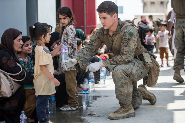 A Marine provides fresh water to a child during an evacuation at Hamid Karzai International Airport, in Kabul, Afghanistan, on August 20. In their first diplomatic talks since the completion of the withdrawal, the Taliban said the United Stats has agreed to provide aid to the Afghan people. File Photo by Sgt. Samuel Ruiz/USMC/UPI