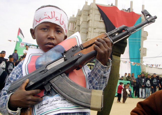 A Palestinian boy poses with an AK-47 assault rifle during a rally organized by Palestinian President Yasser Arafat's Fatah movement, in the Rafah refugee camp in southern Gaza Strip, on February 25, 2002. Photo by Saed Deeb/UPI