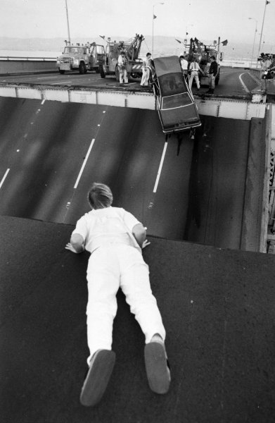 A man watches as a car, which plunged down due to collapsed San Francisco-Oakland Bay Bridge, is being hoisted up after the October 17, 1989, Loma Prieta earthquake. UPI File Photo