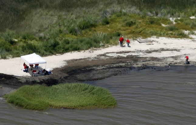 Workers on July 14, 2010, clean up tar balls left on an oil-stained Mississippi beach by the Deepwater Horizon blowout. UPI/A.J. Sisco..