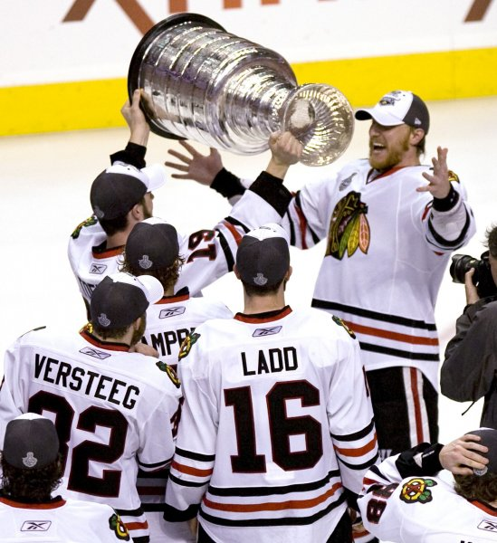 Chicago Blackhawks Marian Hossa reacts as he is presented the Stanley Cup by teammate Jonathan Toews during celebrations on the ice after Chicago defeated the Philadelphia Flyers 4-3 to win the 2010 Stanley Cup in Philadelphia on June 9, 2010. Watching are Andrew Ladd (16) and Kris Versteeg (32). UPI/John Anderson