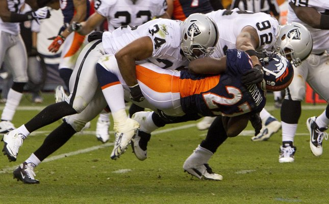 Oakland Raiders safety Mike Mitchell (34) and tackle Richard Seymour pick up and slam Denver Broncos running back Knowshon Moreno to the turf during the second half at Invesco Field at Mile High on October 24, 2010 in Denver. The Raiders decimated the Broncos 59-14. UPI/Gary C. Caskey