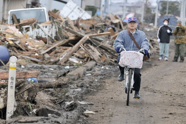 A man rides his bicycle as destruction is seen in Sendai, Miyagi prefecture, Japan, on March 15, 2011. More than 10,000 people are believed to have been killed by a massive earthquake and resulting tsunami. UPI/Keizo Mori