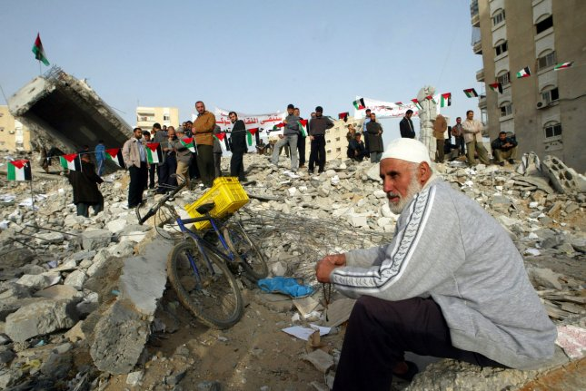 Members of the Palestinian Trade Unions hold a protest against the Israeli blockade on Gaza on top of a building destroyed by an Israeli air strike in Gaza City on March 18, 2008. (UPI Photo/Ismael Mohamad)