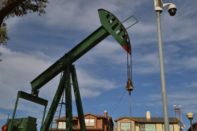 An oil well pumps next to a newly constructed neighborhood near Signal Hill in Long Beach, California in this April photo. OPEC agreed Saturday to continue reduced oil production to keep oil markets stable during the coronavirus pandemic. Photo by Jim Ruymen/UPI