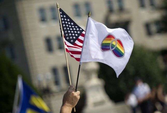 A person holds flags in front of the Supreme Court in Washington, D.C on, June 26, 2013. The Supreme Court ruled DOMA unconstitutional, allowing married same-sex couples to federal benefits, and declining to decide on the California Proposition 8 same-sex marriage case. UPI/Kevin Dietsch