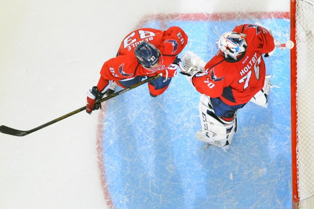 Washington Capitals center Jay Beagle (83) congratulates goalie Braden Holtby (70) following the game at the Verizon Center in Washington, D.C. on April 14, 2016, in the first round of the Stanley Cup playoffs. The Washington Capitals defeated the Philadelphia Flyers, 2-0. Photo by Mark Goldman/UPI