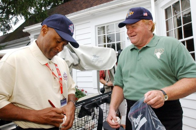 Former St. Louis Cardinals shortstop and Baseball Hall of Famer Ozzie Smith signs a baseball for former New York Mets slugger Rusty Staub before a golf tournament in 2002 at Leatherstocking Golf Course in Cooperstown, N.Y. File photo by Bill Greenblatt/UPI