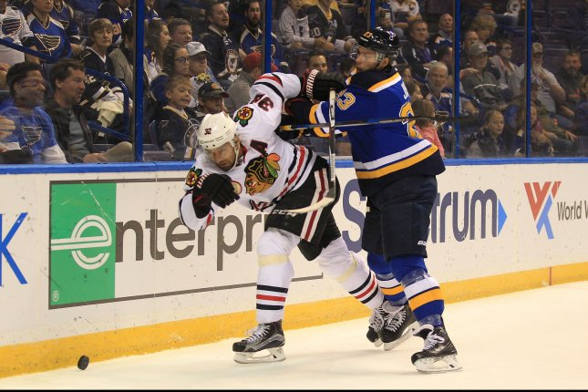 St. Louis Blues Dmitrij Jaskin pushes Chicago Blackhawks Michal Rozsival off of the puck behind the net in the first period at the Scottrade Center in St. Louis on October 8, 2016. Photo by Bill Greenblatt/UPI