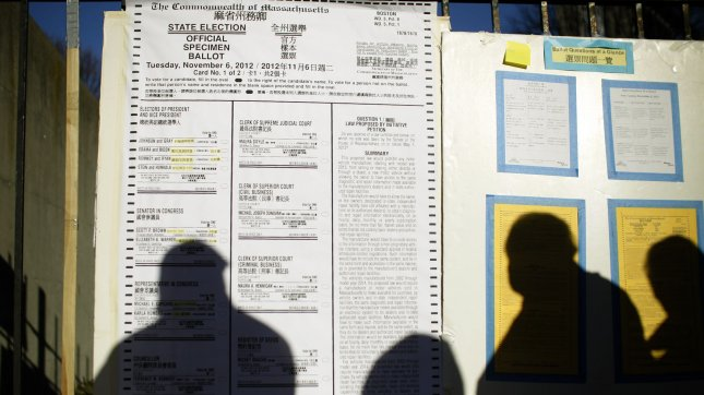 A line of people waiting to vote cast a shadow over a large display of the Massachusetts ballot on election day in Boston, Massachusetts on November 6, 2012. UPI/Matthew Healey