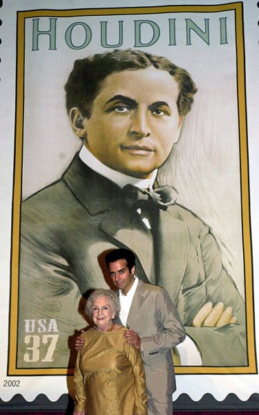 Marie Blood, niece of Harry Houdini, and Illusionist David Copperfield pose in front of a mockup of the U.S. Postal department's new stamp honoring the late illusionist Harry Houdini. (UPI Photo Files/Ezio Petersen)