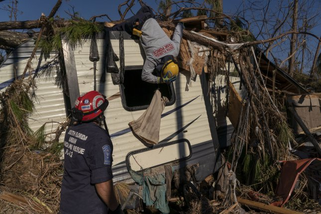 A search-and-rescue team checks a trailer for survivors after Hurricane Michael hit the Florida Panhandle in October. A new smartphone app aims to connect storm victims with rescuers.  File Photo by Ken Cedeno/UPI