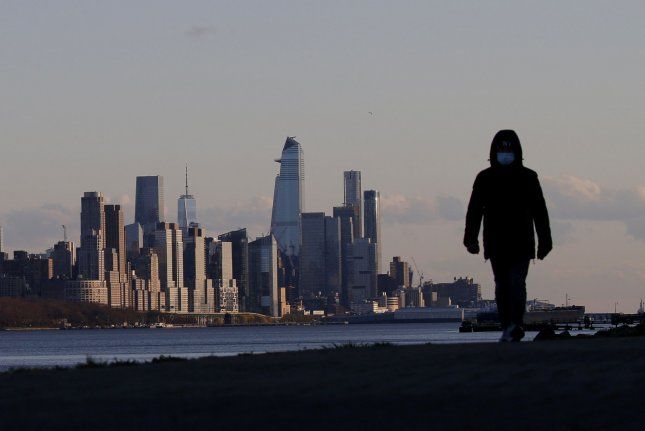 A man wears a protective face mask while walking Thursday along the Hudson River, with the Manhattan skyline in the background, in New York City. Photo by John Angelillo/UPI