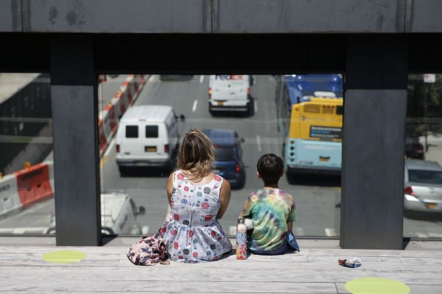 Researchers say the COVID-19 pandemic may drive down life expectancy around the world. Pictured, a woman and child sit between neon yellow circles for social distancing at The High Line in New York City in July. Photo by John Angelillo/UPI