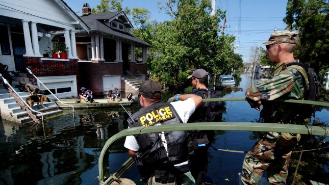 Members of the Oklahoma Army National Guard and agents from the Drug Enforcement Agency wait for the SPCA to remove two dogs prior to checking a home in New Orleans for stranded residents, Sept. 7, 2005. The military and federal agencies are performing house-to-house searches rescuing New Orleans residents stranded in their homes due to flood waters caused by Hurricane Katrina. (UPI Photo/Scott Reed/Air Force).