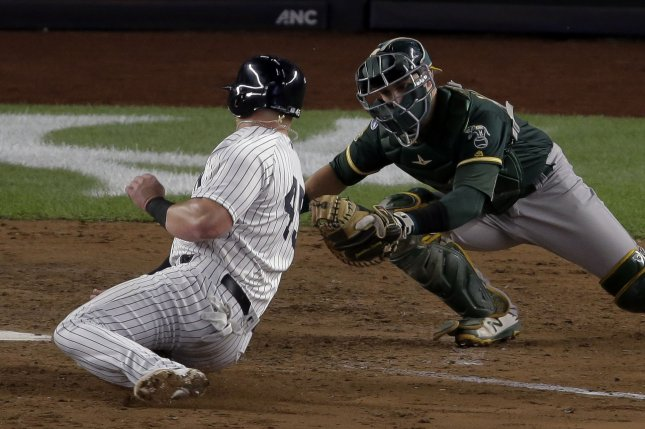 New York Yankees runner Luke Voit scores past Oakland Athletics catcher Jonathan Lucroy (right) in the sixth inning of their MLB American League wild card game on October 3 at Yankee Stadium in New York City. Photo by Ray Stubblebine/UPI