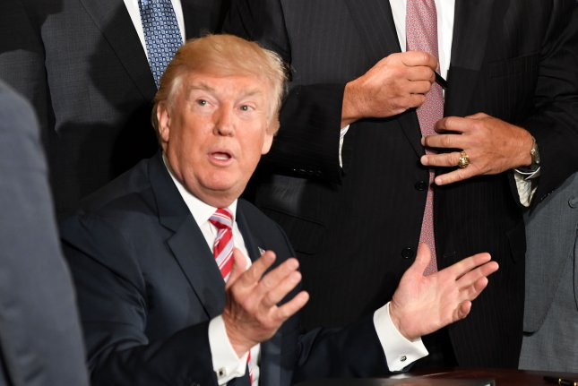 President Donald Trump interacts with members of Congress on Monday before signing a letter of initiative to privatize the nation's air traffic control system during an event in the East Room of the White House. Photo by Pat Benic/UPI
