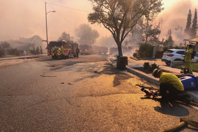 Members of a Santa Barbara County fire crew are seen on November 9, in Calabasas, Calif., fighting the Woolsey Fire. Utility PG&E began widespread power outages Wednesday to mitigate fire danger. File Photo by Capt. Tim Gailey/Santa Barbara County Fire Department