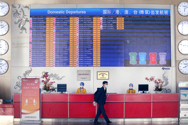Masked workers are seen at an information desk at the Capital Airport in Beijing, China, on October 26, 2020. China is one of several nations that are presently barred from sending travelers to the United States. File Photo by Stephen Shaver/UPI