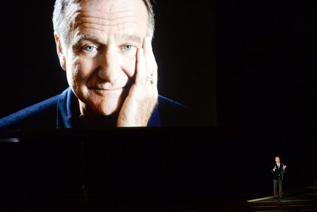 Robin Williams is seen on screen as Billy Crystal speaks in a tribute during the Primetime Emmy Awards at the Nokia Theatre in Los Angeles on Aug. 25. File Photo by Pat Benic/UPI