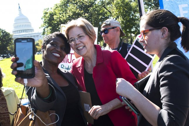 Sen. Elizabeth Warren, D-Mass., greets a protester at a rally in 2017 calling on Congress and the White House to produce a recovery plan for hurricane victims. File Photo by Kevin Dietsch/UPI