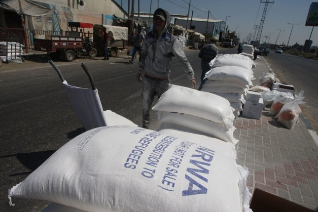 Palestinian men pile bags of flour outside an aid distribution center run by the United Nations Relief and Works Agency in the central Gaza Strip refugee camp of Dair Al Balah, on Wednesday. Photo by Ismael Mohamad/UPI