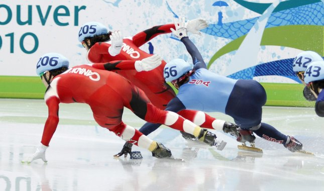 Apolo Anton Ohno of the United States (R) slips as he tries to pass Francois Hamelin of Canada (L) and Charles Hamelin of Canada during the men's 1000 meter short track speed skating final at the 2010 Winter Olympics in Vancouver, Canada on February 20, 2010. Ohno won a bronze medal in the event. UPI/Brian Kersey