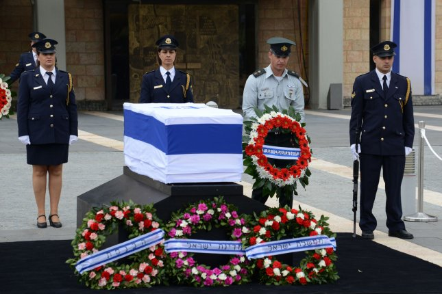 An Israeli defense officer carries a wreath beside the coffin of the late former Israeli Prime Minister Ariel Sharon in the Knesset Plaza, Israel's Parliament, in Jerusalem, Israel, on January 12, 2014. Sharon died January 11, 2014. File Photo by Debbie Hill/UPI