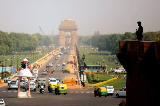 An Indian police officer stands guard on right as traffic moves along a street to India gate in New Delhi, India on March 9, 2009. (UPI Photo/Mohammad Kheirkhah)