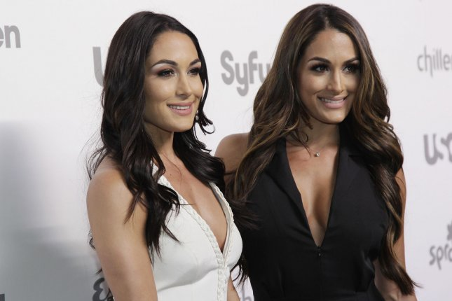 Brie Bella (L) and Nikki Bella arrive on the red carpet at the 2015 NBCUniversal Cable Entertainment Group Upfront on May 14, 2015. Following WWE's weekly flagship program Raw, Brie declared that Nikki will return to the ring after undergoing neck surgery. File Photo by John Angelillo/UPI