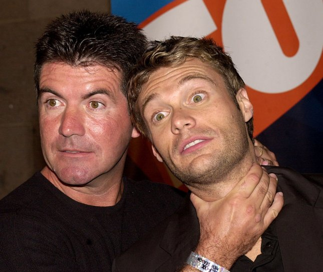 American Idol judge Simon Cowell pretends to strangle the show's host, Ryan Seacrest, in a 2003 photo op. File Photo by Ezio Petersen/UPI
