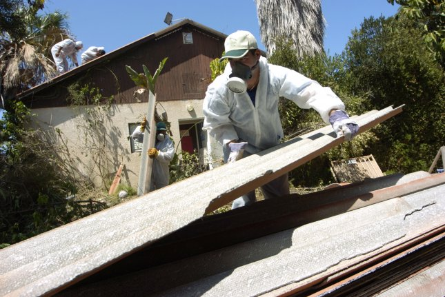 A worker wears protective gear while removing a piece of roofing that contains asbestos. A new report from the CDC shows deaths from asbestos-related exposure are on the rise in young people, but researchers are unsure why considering the series of bans since the 1970s that has limited younger people's exposure. File photo by Debbie Hill/UPI