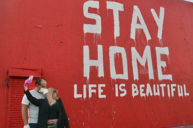 A mural urges residents to stay home as a couple wearing masks kiss while taking a selfie on La Brea Avenue in April 2020. File Photo by Jim Ruymen/UPI