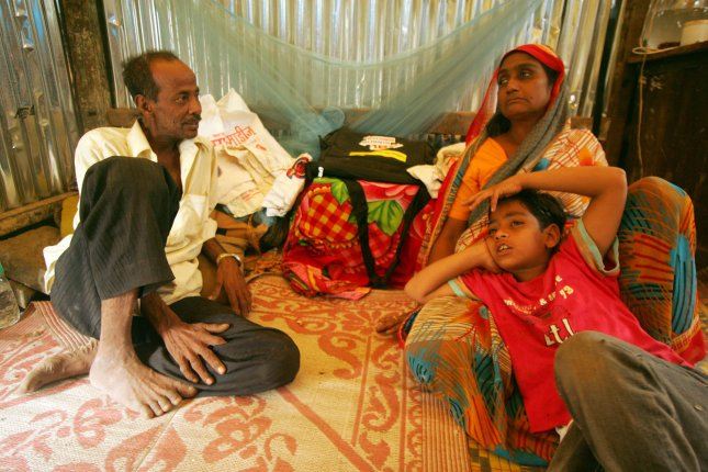 Indian Muslim and Slumdog Millionaire child actor Mohammed Azharuddin Ismail (R) with his father Mohammed Ismail (L) and his mother Shamim Begum take a rest in their slum in East Bandra in Mumbai, India on March 16, 2009. (UPI Photo/Mohammad Kheirkhah)