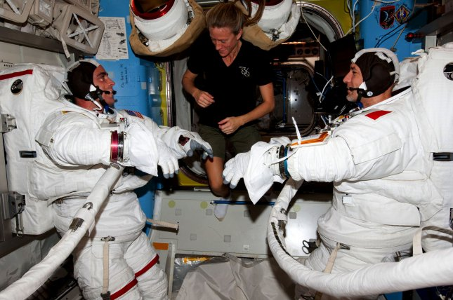 A trio of Expedition 36 flight engineers including NASA astronaut Chris Cassidy (left) and European Space Agency astronaut Luca Parmitano (right), are assisted by NASA astronaut Karen Nyberg, as they prepare for a dry run in the International Space Station's Quest airlock on July 3, 2013. Attired in their Extravehicular Mobility Unit (EMU) spacesuits, Cassidy and Parmitano gear up to participate in the first of two sessions of extravehicular (EVA) scheduled for July 9 and July 16, 2013.