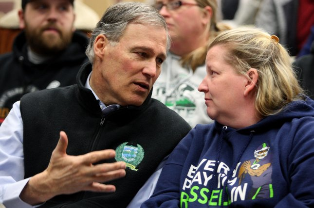 Washington Gov. Jay Inslee (R) talks to a resident during a prayer vigil for victims of a mudslide in 2014 that buried the town of Oso, Wash. File Photo by Jim Bryant/UPI