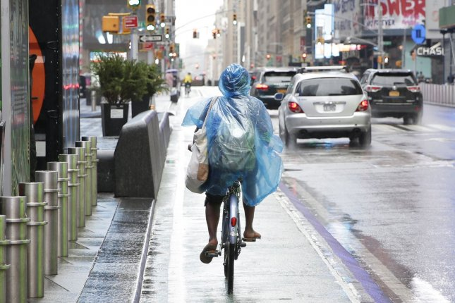 A cyclist wears a plastic rain covering while riding in Times Square as Tropical Storm Fay approaches New York City on Friday. Photo by John Angelillo/UPI