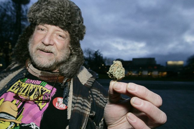 Michael Dare, a medical marijuana user, displays a bud during a public consumption rally after Washington state jumped into history becoming the first state, along with Colorado, to legalize recreational marijuana use. (Jim Bryant/UPI)