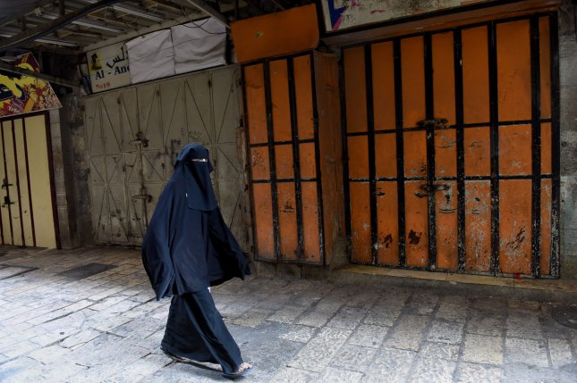 A Palestinian woman walks past closed shops during a general strike Monday against Israel's Nation State Law, which declares that only Jews have the right of self-determination in Israel. Photo by Debbie Hill/UPI
