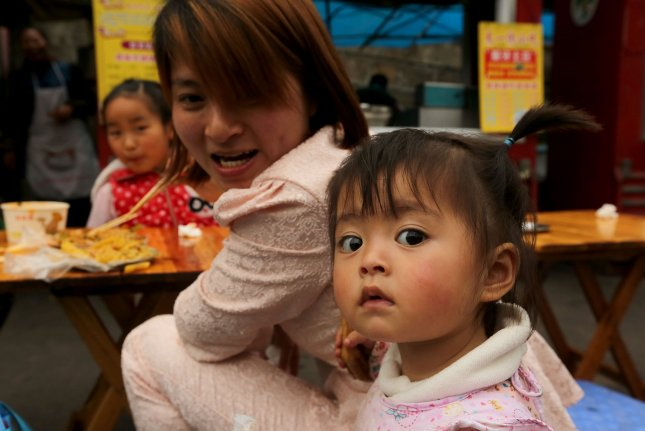 A young Chinese girl has lunch with her family in Jiayang, a small mountainous city in Sichuan Province. China, the world's most populous country, has a relatively small youth demographic, which was partially the result of China's one-child policy. File Pphoto by Stephen Shaver/UPI