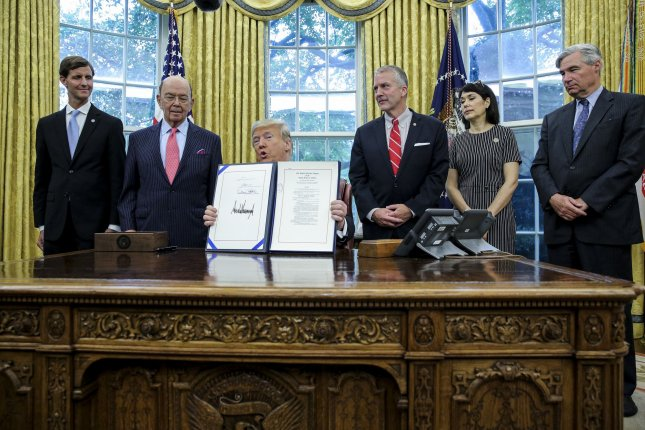 """President Donald Trump holds up a signed S. 3508, the """"Save Our Seas Act of 2018"""" during a ceremony in the Oval Office of the White House on Thursday. Photo by Oliver Contreras/UPI"""