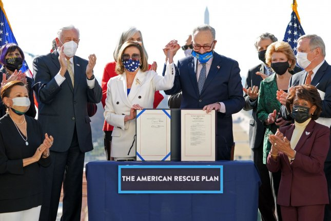 Speaker of the House Nancy Pelosi, D-Calif., and Senate Majority Leader Charles Schumer, D-N.Y., celebrate with fellow Democrats during an enrollment ceremony for the American Rescue Plan at the U.S. Capitol on March 10. File Photo by Kevin Dietsch/UPI