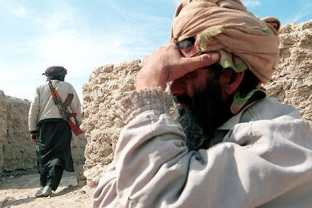 A Taliban soldier (Left) stands guard in front of his commander's residence at the Makaki refugee camp set up by the Iranian Red Crescent Society, 3 kilometers (2 miles) inside Afghanistan from the Iranian border, Monday, Oct. 29, 2001. rlw/ak/Ali Khalig UPI