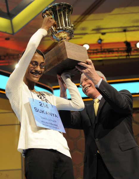 Sukanya Roy, 14, an 8th grader in Wilkes-Barre, PA, (L) lifts the trophy, assisted by EW Scripps Company President and CEO Rich Boehne after winning the 2011 Scripps National Spelling Bee, June 2, 2011, in National Harbor, MD. Roy won by correctly spelling the word cymotrichous , meaning having wavy hair. UPI/Mike Theiler