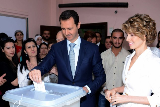 In this photo released by Syria's national news agency, Syrian President Bashar al-Assad and Syrian first lady Asma Assad vote in the country's presidential election at a polling station in Maliki, a residential area in the center of the capital Damascus, Syria, on June 3, 2014, Syrians lined up outside polling centers in government-controlled areas around the country to vote Tuesday in the presidential election that Assad is widely expected to win but which the exiled opposition has slammed as a farce. (UPI)