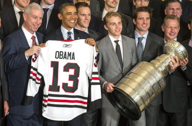 President Barack Obama (2nd-L) holds a jersey given to him by the Chicago Blackhawks with Blackhawks President and CEO John McDonough (L), team captain Jonathan Toews (3rd-L) and center Patrick Kane (3rd-L) at an event where Obama honored the 2013 Stanley Cup Champions Chicago Blackhawks, at the White House in Washington on November 4, 2013. UPI/Kevin Dietsch