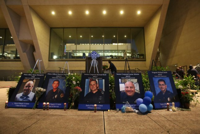 Portraits of the five slain officers are shown in front of the speakers platform during a candle light vigil outside City Hall in Dallas, Texas on July 11, 2016. The Dallas officers killed are part of the 32 officers killed by firearms so far in 2016, a 78 percent increase from the previous year. Photo by Chris McGathey/UPI