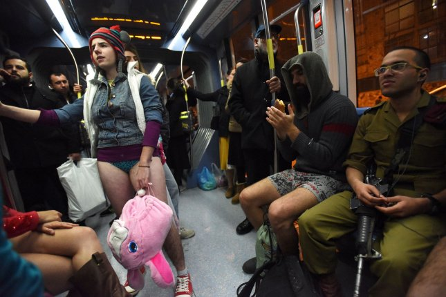 A soldier sits near Israelis riding the Jerusalem light rail without wearing pants while taking part in the No Pants Subway Ride in Jerusalem on Sunday. The event, started in 2002, by the Improv Everywhere comedy group and has spread to over 25 international countries. Photo by Debbie Hill/UPI