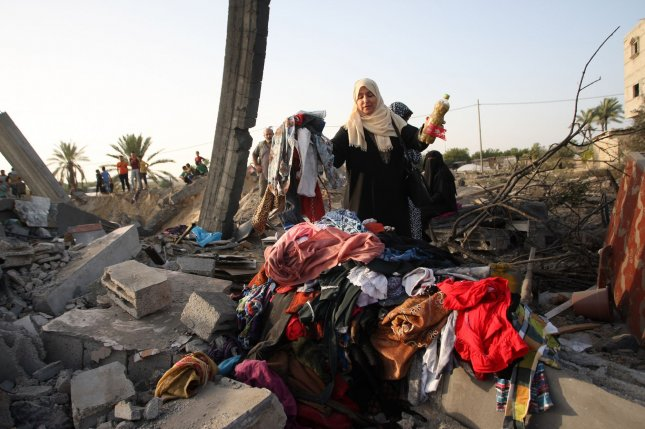 Palestinian woman collects clothes from her house that was destroyed in an Israeli air strike on Khan Yunis in the southern Gaza on Wednesday. Photo by Ismael Mohamad/UPI.